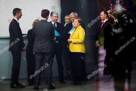 German Chancellor Angela Merkel talks to her staff as she waits for the arrival of Georgian Prime Minister Giorgi Kvirikashvili for talks at the chancellery in Berlin