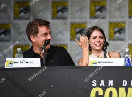 "John Barrowman, left, and Willa Holland attend the ""Arrow"" panel on day 3 of Comic-Con International, in San Diego"