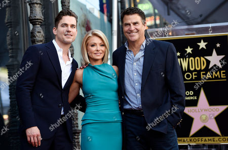 Television personality Kelly Ripa, center, poses with actors Matt Bomer, left, and Ted McGinley during a ceremony to award her a star on the Hollywood Walk of Fame, in Los Angeles