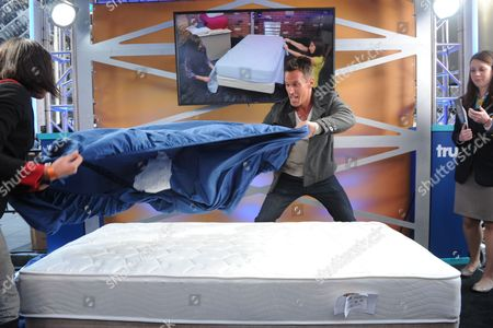 Dan Cortese, center, host of truTV's Guinness World Records Unleashed, attempts the fastest time for a team of two people to make a single bed at the truTV event celebrating the premiere of the Guinness World Records Unleashed series, in New York's Times Square