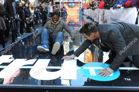 Dan Cortese, right, host of truT's Guinness World Records Unleashed, cheers on a participant of the fastest 20-meter butt scoot at the truTV & GUINNESS WORLD RECORDS event celebrating the premiere of the Guinness World Records Unleashed series, in New York's Times Square