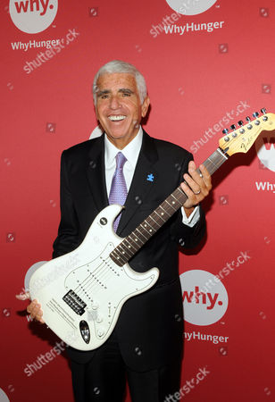 Mel Karmazin, CEO of SiriusXM Satellite Radio, receives a Fender guitar representing his 2012 WhyHunger-Chapin Award while being honored at WhyHunger's annual awards dinner, in New York