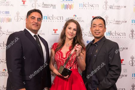 """Cenk Uygur, left, Ana Kasparian, and Steve Oh pose with the 2016 Vision award for """"The Young Turks"""" at the 31st Annual Imagen Awards ceremony, in Beverly Hills, CA"""