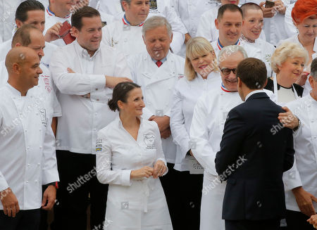 French President Emmanuel Macron, right, shakes hands with chef Alain Ducasse while the son of Paul Bocuse Jerome Bocuse looks on during an event at the Elysee Palace in Paris, . 180 top chefs were invited to the Elysee Palace to promote the French cuisine. Bodyguard left