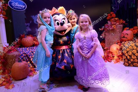From left, Crystal Burge, Luna Marie and Mia Talerico pose with Minnie Mouse at Disney Store Halloween BOOtique Party, in Glendale, CA