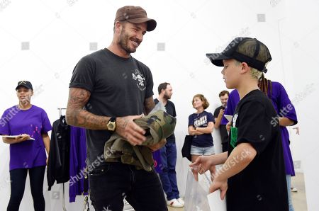 """David Beckham and his son Cruz shop for clothes at Kanye West's """"Pablo"""" pop-up shop, in Los Angeles. The rapper-turned-fashion mogul announced plans to open 21 stores worldwide just for this weekend to sell clothing based on his latest album, """"The Life of Pablo"""