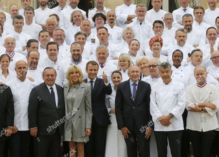 From left, chef Jerome Because son of Paul Bocuse, businessman Olivier Ginon, the wife of French President Brigitte Macron French President Emmanuel Macron, French Interior Minister Gerard Collomb, chef Regis Marcon and chef Joel Robuchon posess for a group photo during an event at the Elysee Palace in Paris, France, 27 September 2017. 180 top chefs were invited to the Eylsee Palace to promote the French cuisine.