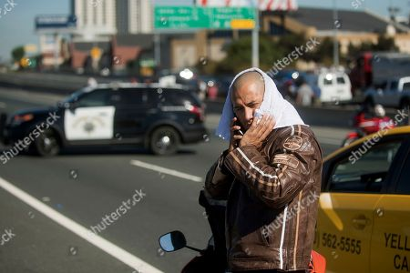 Stranded motorcyclist David Carr waits for Interstate 80 to reopen as police investigate the scene of a standoff with a suspect driving a sports utility vehicle, in Emeryville, Calif. The incident, which ended in gunfire, shut freeway traffic in both directions at the height of morning rush hour