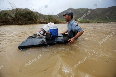 Stock Photo of Manolo Gonzales crosses through the Rio San Lorenzo de Morovis, since the bridge that crosses the river was swept away by Hurricane Maria, in Morovis, Puerto Rico