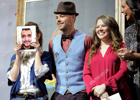 """Maria Barracuda, far left, hides behind a live iPad image of her partner Jorge """"La Chiquis"""" Amaro in the Mexican pop group Jotdog, onstage at The XIII Annual Latin Grammy Awards nominations at the Belasco Theater, in Los Angeles. Looking, from left, are Jesse and Joy Huerta of Mexican pop duo Jesse & Joy and Spanish singer Shaila Durcal. The show will be held on Nov. 15 in Las Vegas"""