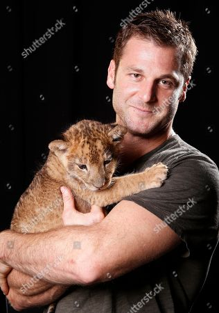 """Canadian large predator animal expert, television producer and star of Animal Planet's """"Frontier Earth"""" Dave Salmoni and his baby lion pose for a portrait, on in New York"""