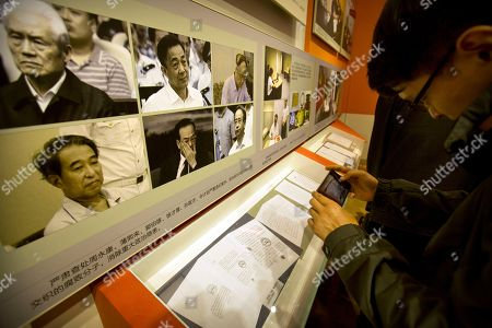A man takes a photo of a display showing Chinese leaders who have been convicted of various crimes at an exhibition highlighting China's achievements under five years of leadership by Chinese President Xi Jinping at the Beijing Exhibition Hall in Beijing, . The exhibition comes ahead of a Communist Party congress in October during which Xi is expected to be confirmed for a second five-year term as China's head of state. Clockwise from top left is Zhou Yongkang, Bo Xilai, Guo Boxiong, Xu Caihou, Sun Zhengcai, and Ling Jihua