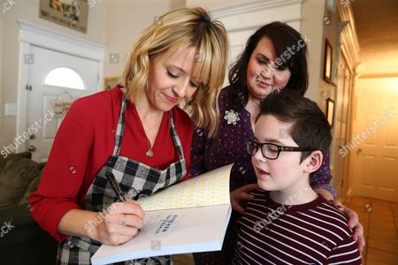 Celebrity Chef Kelsey Nixon autographs a cookbook for Kelly Tillotson and her son Brigham at Nature's Harvest bread's Kitchen Crash, in Forney, TX