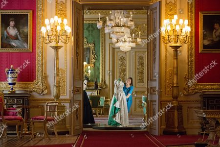 Editorial image of Fashioning A Reign: 90 Years Of Style From The Queen's Wardrobe At Windsor Castle - The Green Drawing Room Curator Caroline De Guitaut Adjusting A 1961 Norman Hartnell Dress Worn By The Queen At A State Banquet In On Her State Visit To Pakistan.
