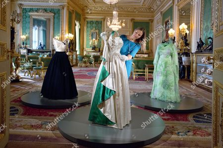 Editorial photo of Fashioning A Reign: 90 Years Of Style From The Queen's Wardrobe At Windsor Castle - The Green Drawing Room Curator Caroline De Guitaut Adjusting A 1961 Norman Hartnell Dress Worn By The Queen At A State Banquet In On Her State Visit To Pakistan. On