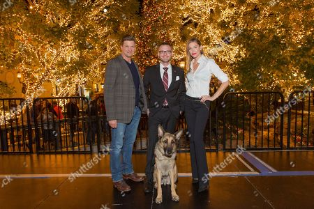 """Stock Picture of Marc Blucas, from left, Captain Jason Haag, service dog Axel and Tricia Helfer attend a screening for Hallmark Movies & Mysteries """"Operation Christmas"""" at The Gove on in Los Angeles"""