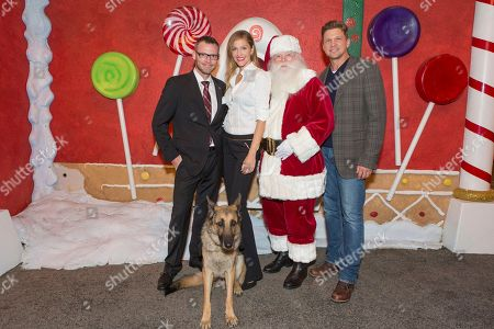 """Captain Jason Haag with service dog Axel, from left, Tricia Helfer and Marc Blucas attend a screening for Hallmark Movies & Mysteries """"Operation Christmas"""" at The Gove on in Los Angeles"""