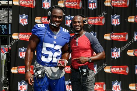 NY Giants' Jon Beason, left, and actor Taye Diggs call a play on a Duracell Quantum enabled headset at MetLIfe Stadium where more than 650 Duracell Quantum batteries are used per game, on Wed, in E.Rutherford, N.J