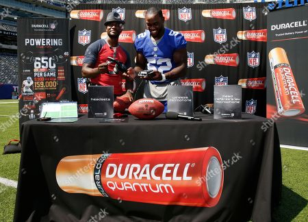 New York Giants' Jon Beason, right, demonstrates the communication devices that are powered by Duracell Quantum batteries to actor Taye Diggs at MetLife stadium on Wed., in E.Rutherford, N.J. More than 650 of these batteries power every NFL game