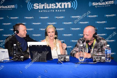 Jenny McCarthy, center, her husband Donnie Wahlberg, left, and Pawn Stars Rick Harrison talk during the broadcast of Dirty, Sexy, Funny with Jenny McCarthy on SiriusXM at the Consumer Electronics Show at the Las Vegas Convention Center on in Las Vegas