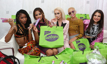Simone Battle, and from left, Emmalyn Estrada, Lauren Bennett, Paula Van Oppen and Natasha Slayton, of the musical group G.R.L., stop by the Wango Tango gifting suite to taste the new Randoms candy by Wonka at StubHub Center, in Carson, Calif
