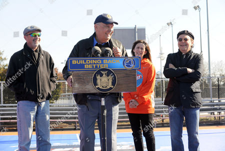 Billy Crystal, right, his wife Janice, and brothers Richard, left, and Joel Crystal, at podium, attend the opening ceremony for two new DreamCourts, in Long Beach, N.Y. The courts were constructed and opened today, one-year post Hurricane Sandy, thanks to the Nancy Lieberman Foundation, WorldVentures Foundation and Billy and Janice Crystal