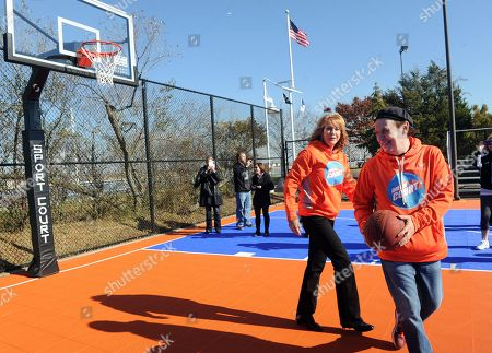 Basketball Hall of Famer and founding partner of DreamCourts, Nancy Lieberman, left, plays a game of basketball with Billy Crystal at the opening ceremony for two new DreamCourts, in Long Beach, N.Y. The courts were constructed and opened today, one-year post Hurricane Sandy, thanks to the Nancy Lieberman Foundation, WorldVentures Foundation and Billy and Janice Crystal