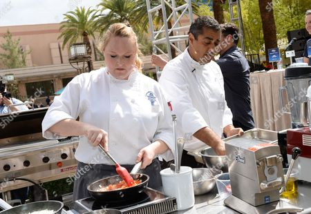 Chef Michael Mina and Le Cordon Bleu student Krista Burdick compete at the Chase Sapphire Preferred Grill Challenge at Emeril's New Orleans Seafood Extravaganza during Vegas Uncork'd by Bon Appetit, at MGM Grand on in Las Vegas