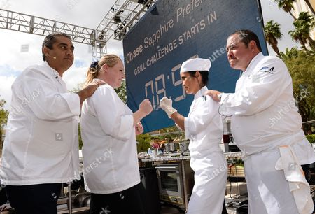 Chefs Michael Mina, left, and Emeril Lagasse prep their culinary students Krista Burdick, left, and Elsa Sabellano Jenstad for the Chase Sapphire Preferred Grill Challenge at Emeril's New Orleans Seafood Extravaganza during Vegas Uncork'd by Bon Appetit, at MGM Grand on in Las Vegas
