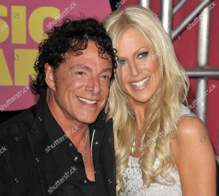 Neal Schon, left, and Michaele Salahi arrive at the CMT Music Awards in Nashville, Tenn. San Francisco supervisors are considering a $290,000 payout to settle a lawsuit by Schon, the guitarist of rock band Journey over his lavish 2013 wedding to the former reality television star, Salahi. A committee of the Board of Supervisors is scheduled to take up the proposed settlement