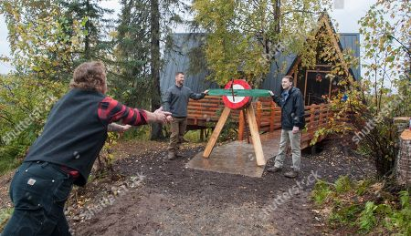 """Lumberjack Boone Scheer throws an ax during the ribbon cutting ceremony for Princess Cruises, celebrating the new treehouse developed in collaboration with Animal Planet's """"Treehouse Masters."""" Honorary ribbon holders included Animal Planet's Dave Salmoni (left) and Lodge General Manager Richard Peterson (right"""