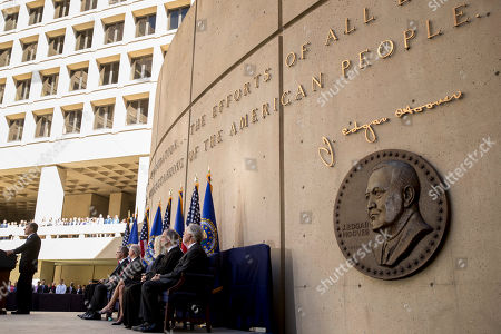 A depiction of former FBI Director J. Edgar Hoover is displayed as FBI Director Chris Wray, left, speaks at his installation ceremony at the FBI Building, in Washington