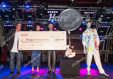 Michael Beacham, Sr. Vice President and COO of Corporate Cafes for Hard Rock International, presents a check to Cindy Blackman Santana and rock legend, Carlos Santana for The Milagro Foundation during a meet and greet held at Hard Rock Cafe Las Vegas Strip. Money donated to The Milagro Foundation, founded by Carlos Santana, supports art, education and health programs for families