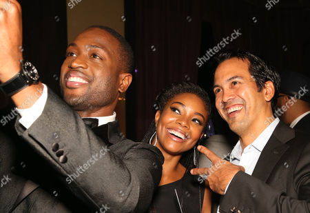 Dwyane Wade, Gabrielle Union and Erik Spoelstra, Coach of the Miami Heat, pose for a photo during the RunWade Fashion Show on in Miami, Fla