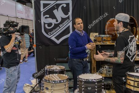 """Marcus Lemonis, left, of the TV show """"The Prophet"""" films at the SJC Custom Drums booth during the 2015 National Association of Music Merchants (NAMM) show at the Anaheim Convention Center on in Anaheim, Calif"""