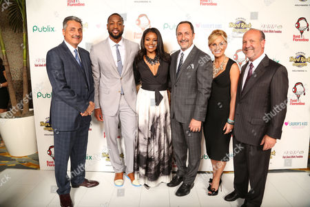 Tony Fiorentino, Miami Heat Broadcaster, Dwyane Wade, of the Miami Heat, Gabrielle Union, Eric Reid, Miami Heat Broadcaster, Lauren Book, Founder and CEO of Lauren's Kids and Ron Book, Chairman of Lauren's Kids, attend the 8th Annual Reid & Fiorentino Call of the Game Dinner Presented by Publix on at the Seminole Hard Rock Hotel & Casino in Hollywood, Fla