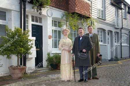 British actor Robert Powell, centre, dressed as the character Poirot, poses at a photo call for Agatha Christie's first ever play, Black Coffee. Alongside Powell are actors Liza Goddard, as Miss Caroline Amory, and Robin McCallum, right, as Poirot's friend and confidante Captain Arthur Hastings. The photo call took place outside the former west London residence of author Christie, in Cresswell Place, London