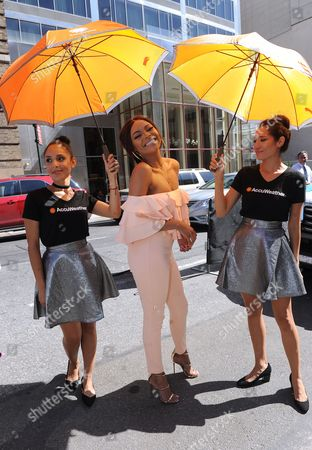 Bonang Matheba is shaded from the hot summer sun by AccuWeather's MinuteCast umbrellas at New York Fashion Week, in New York. The AccuWeather MinuteCast Street Team is at it again helping Fashion Week attendees stay stylish and one-step ahead of any possible precipitation