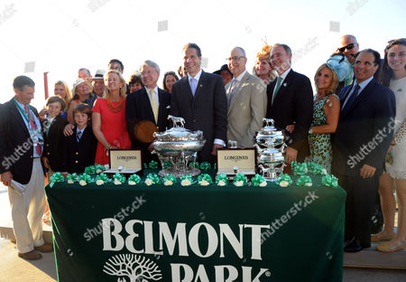 Tonalist owner Robert Evans, center left, and New York Governor Andrew Cuomo, center, attend the trophy presentation after Tonalist won the 146th Belmont Stakes, beating out Triple Crown hopeful California Chrome, at Belmont Park in New York. Longines, the Swiss watchmaker known for its elegant timepieces, is the Official Watch and Timekeeper of the 146th running of the Belmont Stakes and the Triple Crown