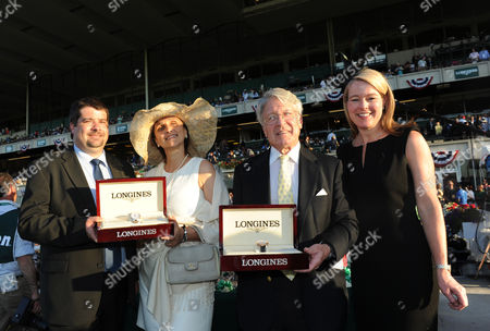 Tonalist owner Robert Evans, second right, and Valerie Clement, second left, wife of trainer Christophe Clement, are presented Longines timepieces by Jennifer Judkins, right, and Sebastien Zbinden, left, both of Longines, after Tonalist won the146th Belmont Stakes, at Belmont Park in New York. Longines, the Swiss watchmaker known for its elegant timepieces, is the Official Watch and Timekeeper of the 146th running of the Belmont Stakes