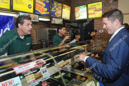 SUBWAY Famous Fans Mike Golic, left, and Mike Greenberg, center, of ESPN, work behind the counter at a SUBWAY restaurant in New York, as guest sandwich artists as part of the FOOTLONGS and Football ANYone? event celebrating SUBtember, where any regular footlong sandwich is $5 all month long