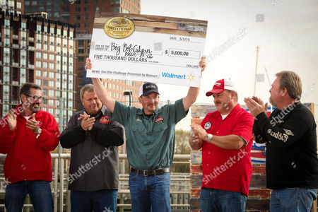 Big Bob Gibson Bar-B-Q team captain, Chris Lilly, of Decatur Ala., celebrates his One Bite Challenge win presented by Walmart and poses with a $5000 check during the Kingsford Invitational on at Hudson River Park's Pier 26 in New York. To win, he grilled a USDA Choice Premium steak which represented his home regional style
