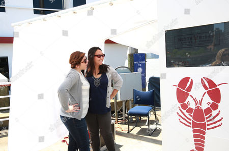 Claudia Ponce and Amanda Gordon pose at the photobooth at the launch of North River Lobster Company, New York City's first ever floating lobster shack, at Pier 81 on in New York