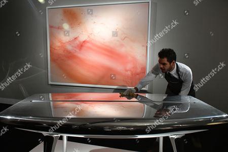(Background) Wolfgang Tillmanns. Urgency XVI. Est. £300,000-500,000. (Foreground) Marc Newson. Event Horizon Table. Est. £100,000-150,000