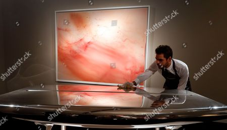 An employee polishes an artwork by Marc Newson called 'Event Horizon Table' in front of a painting by Wolfgang Tillmans called 'Urgency XVI' at Christies's auction rooms in London, . The artworks will be auctioned on Oct. 3 in the Masterpieces of Design and Photography sale