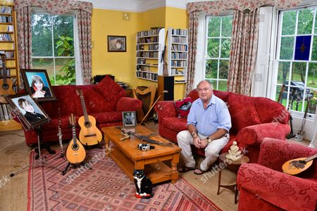 LOUIS DE BERNIERES 'MY HAVEN'-LIVING ROOM OF HIS NORFOLK HOME 13.9.2016 Portraits of his children Robin & Sophie  Mandolin, Guitar, and Flute Fake 'Renoir' Painting Air Rife Golf Club Photo of LdB and his Ford Popular Machete Knife, Knife from Turkey and his Camera Cat Door stop Sculpture by Emily Young Garden Spade His cat 'Basil' (only in a few frames)