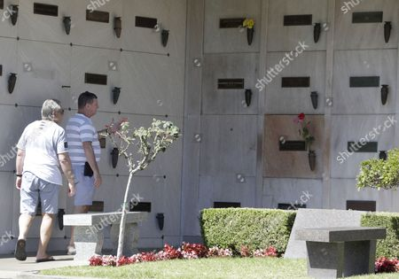 Visitors look at the grave (with flowers) of US actress Marilyn Monroe which is next to the empty crypt where the late Playboy magazine founder Hugh Hefner will be buried at the Pierce Brothers Westwood Village Memorial Park and Mortuary in Los Angeles, California, USA, 29 September 2017. Hefner bought the plot in 1992 for 75,000 USD and has said 'Spending eternity next to Marilyn is too sweet to pass up'. Hefner died of natural causes at the age of 91 in Los Angeles on 27 September 2017.