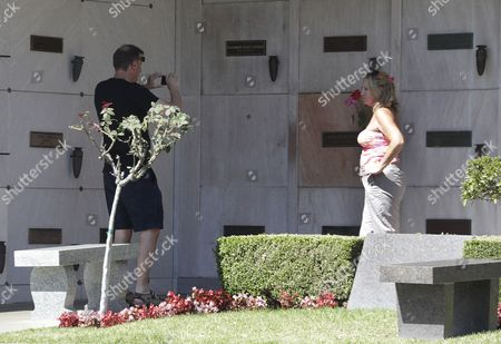 A woman poses for a photo at US actress Marilyn Monroe's grave next to the empty crypt where the late Playboy magazine founder Hugh Hefner will be buried at the Pierce Brothers Westwood Village Memorial Park and Mortuary in Los Angeles, California, USA, 29 September 2017.  Hefner bought the plot in 1992 for 75,000 USD and has said 'Spending eternity next to Marilyn is too sweet to pass up'. Hefner died of natural causes at the age of 91 in Los Angeles on 27 September 2017.
