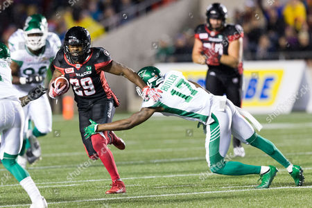 Ottawa Redblacks William Powell (29) runs the ball while Saskatchewan Roughriders Crezdon Butler (17) dives to attempt a tackle during the CFL game between Saskatchewan Roughriders and Ottawa Redblacks at TD Place Stadium in Ottawa, Canada. Saskatchewan won the game 18-17 with a late rouge