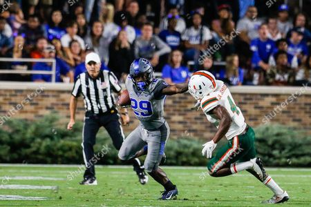 Shaun Wilson (29) of the Duke Blue Devils stiff arms Jaquan Johnson (4) of the Miami Hurricanes in the NCAA matchup between Miami and Duke at Wallace Wade Stadium in Durham, NC